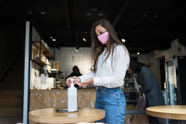 woman using sanitizer gel cleans hands coronavirus virus cafe